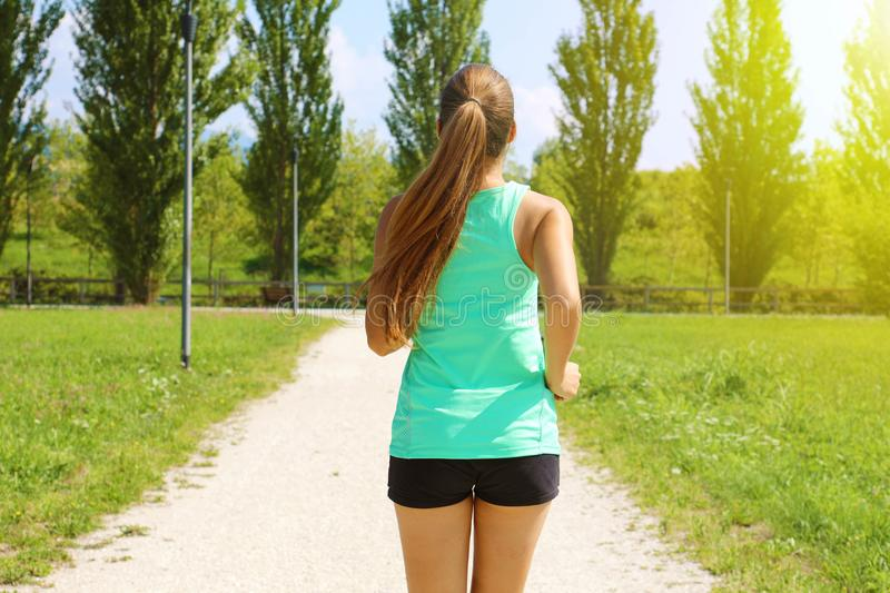 Young sporty woman running in park. Fitness girl jogging in park. Rear view of sporty girl running on pathway stock photos