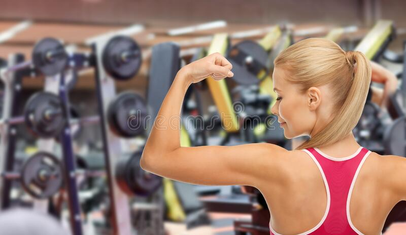 Young sporty woman showing her biceps in gym stock photos