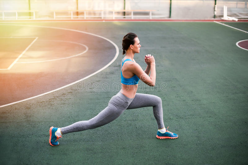 Young sporty woman in sportswear exercising on stadium stock photo