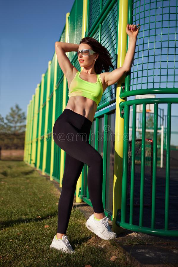 Young sporty woman standing near a football field. Female model in sportswear exercising outdoors. stock photography
