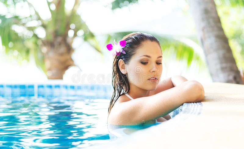 Beautiful woman relaxing in a pool at summer stock image