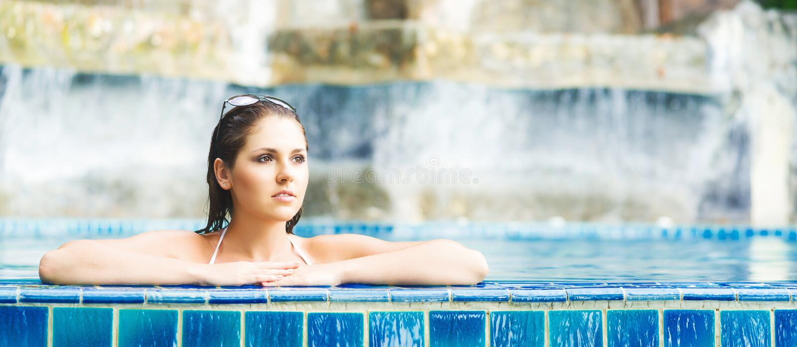 Beautiful woman relaxing in a pool at summer royalty free stock photography