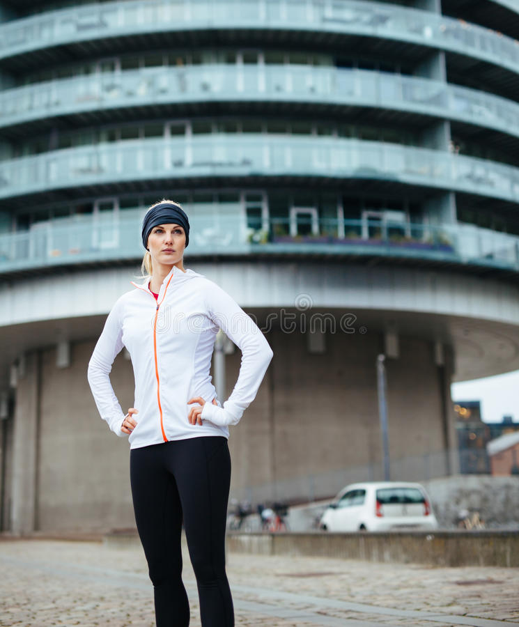 Young sporty woman taking a break after workout outdoor. S. Caucasian female athlete on street looking away stock photography