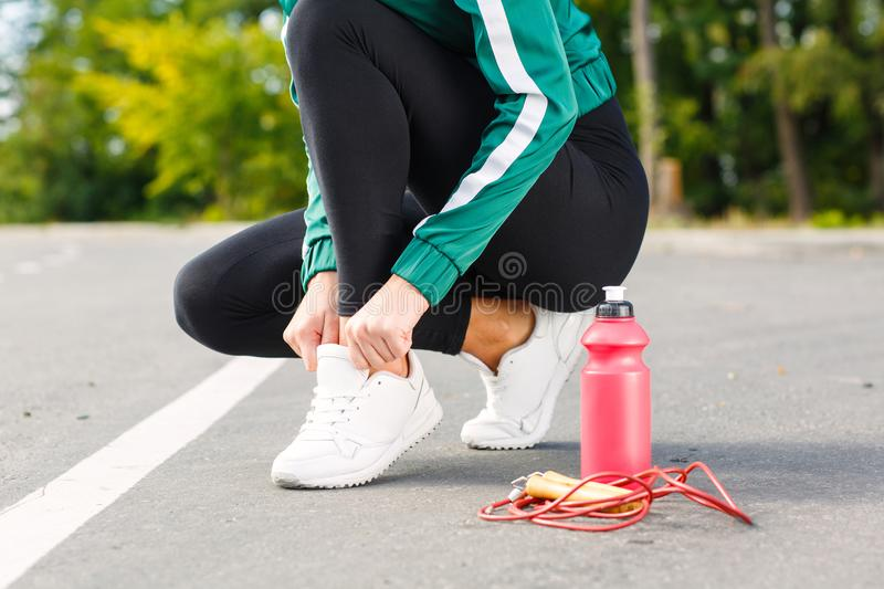 A young sporty woman ties up shoelaces on sneakers. A girl with perfect body doing exercises. stock images