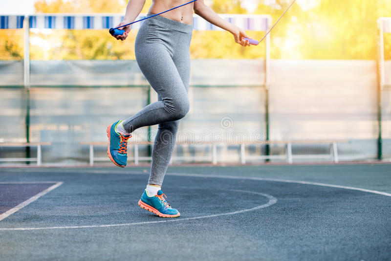 Young sporty woman training with skipping rope on stadium. Low section of young sporty woman training with skipping rope on stadium royalty free stock photos