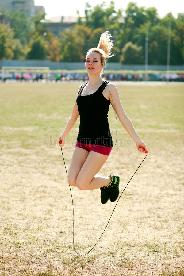 Young sporty woman workout, jumping over rope royalty free stock photo