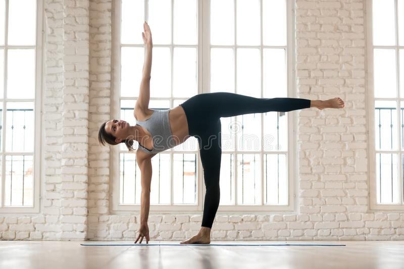 Young sporty yogi woman practicing yoga, doing Half Moon exercis. E, Ardha Chandrasana pose, working out, wearing sportswear, pants and top, indoor full length stock photos