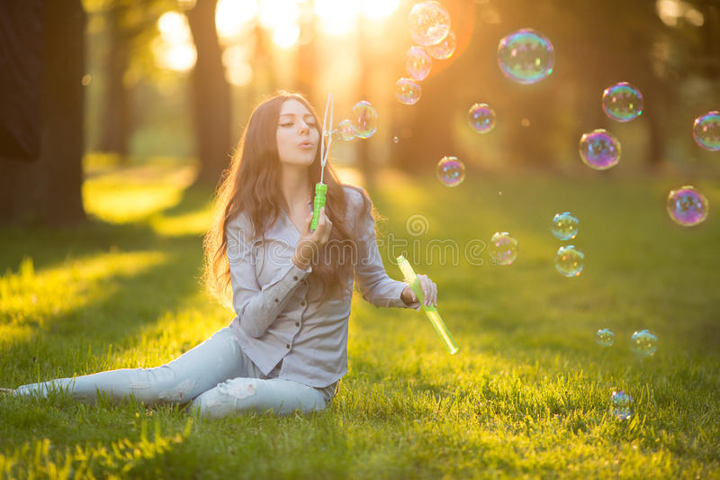 Young spring fashion casual woman blow bubbles in the sunset in. Park Springtime Summertime Trendy girl sitting on grass in sunset Spring summer landscape stock images