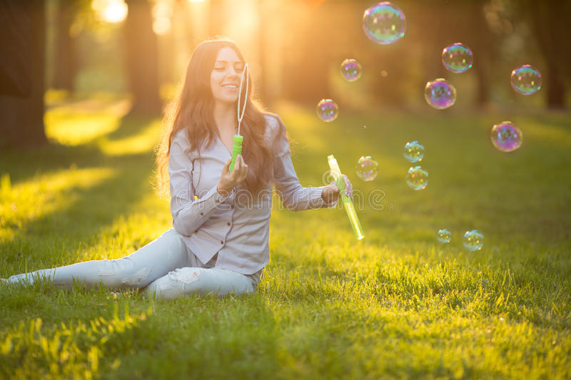 Young spring fashion casual woman blow bubbles in the sunset in. Park Springtime Summertime Trendy girl sitting on grass in sunset Spring summer landscape royalty free stock photography