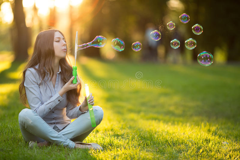 Young spring fashion casual woman blow bubbles in the sunset in. Park Springtime Summertime Trendy girl sitting on grass in sunset Spring summer landscape royalty free stock photos