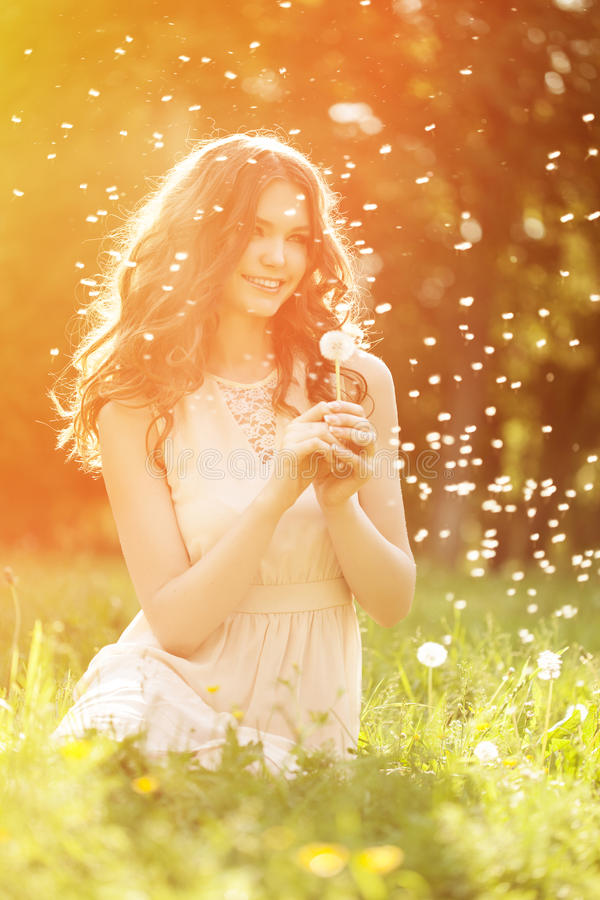 Young spring fashion woman blowing dandelion in spring garden. S. Pringtime. Trendy girl at sunset in spring landscape background. Allergic to pollen of flowers stock images