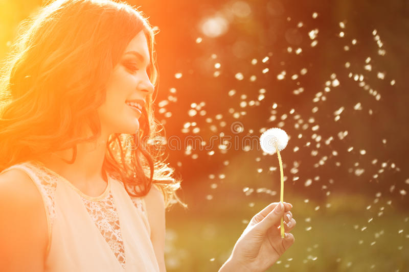 Young spring fashion woman blowing dandelion in spring garden. S royalty free stock image