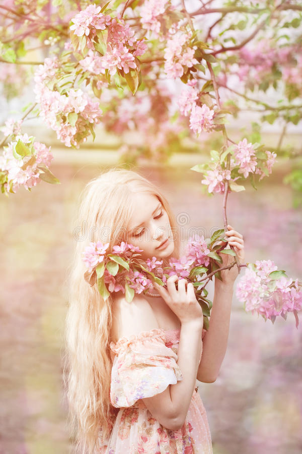 Young spring fashion woman in spring garden. Springtime. Trendy. Girl at sunset in spring landscape background. Allergic to pollen of flowers. Spring allergy stock photography