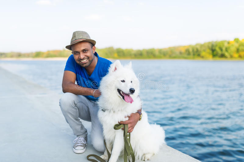 The young Sri Lankan and his fluffy dog have a rest in the park on the river bank. stock photos
