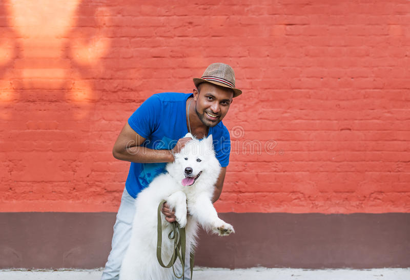 Young Sri Lankan and his fluffy white dog against the background of a red brick wall. royalty free stock image