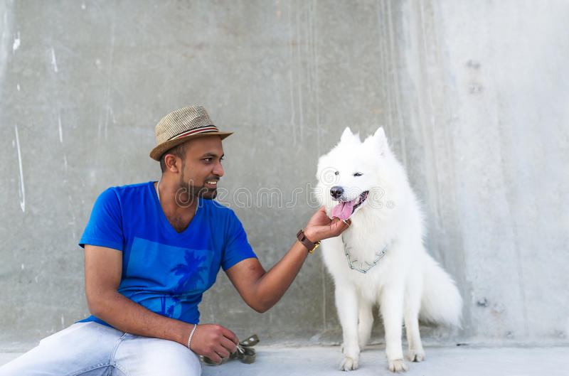 Young Sri Lankan and his fluffy white dog. royalty free stock photography