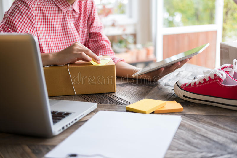 Start up small business owner checking product order at workplace. freelance woman entrepreneur SME seller prepare parcel box for. Young start up small business royalty free stock photo