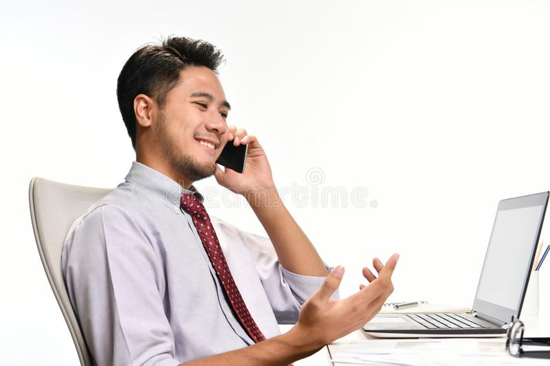 Young business man smiling while talking on the phone and working with laptop computer royalty free stock images