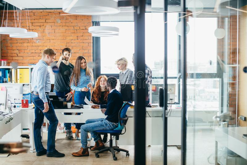 Young startup founders are learning to create profitable business. In room with glass wall. business activity.business proposition royalty free stock photo
