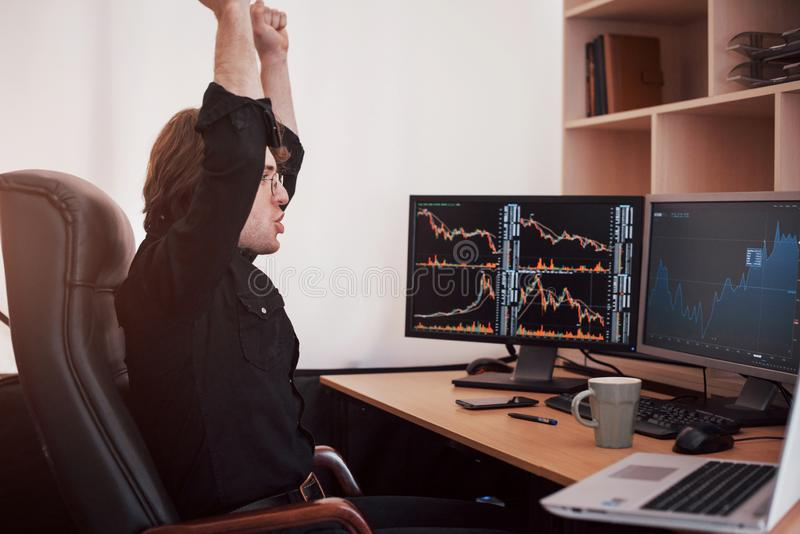 Young stock trader broker stretching hands at workplace, he first achieved great success on the stock market royalty free stock images