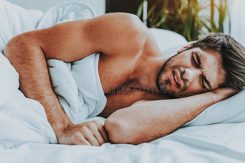 Young strained male lay in bed and see bad dream. Sleep disorder concept. Close up portrait of young strained man suffering from nightmare while laying in bed royalty free stock photo
