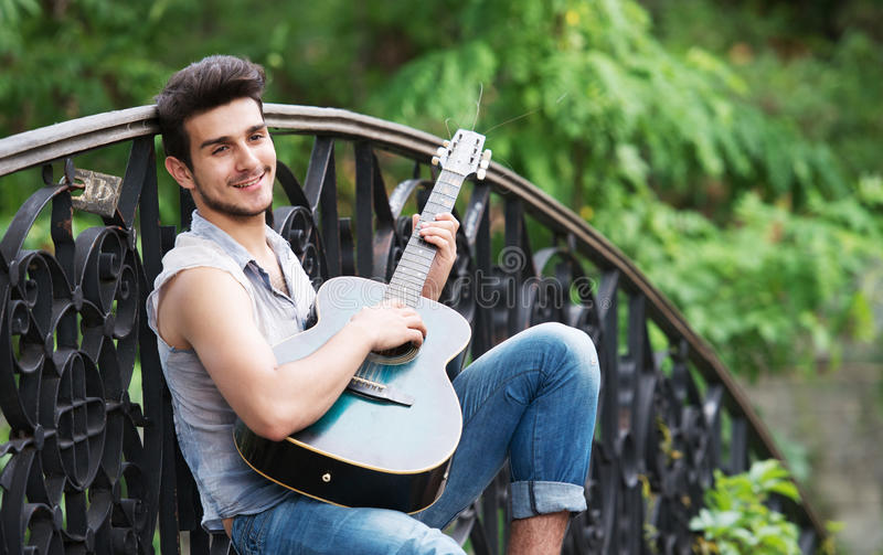 Young street guitarist. Portrait of a young guitarist playing on the bridge and smiling at camera royalty free stock photography