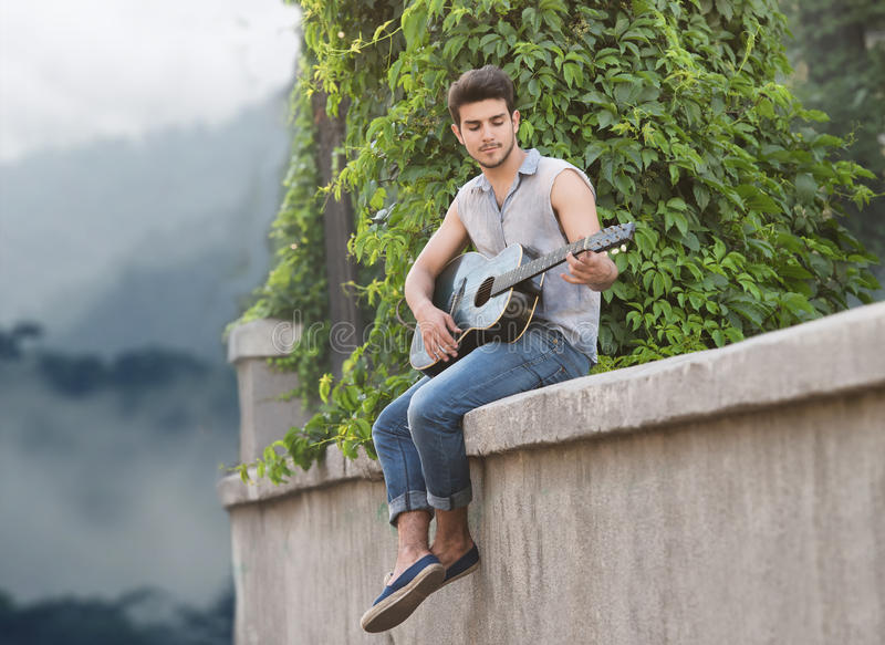 Young street guitarist. Portrait of a young guitarist sitting on parapet and looking at camera stock image