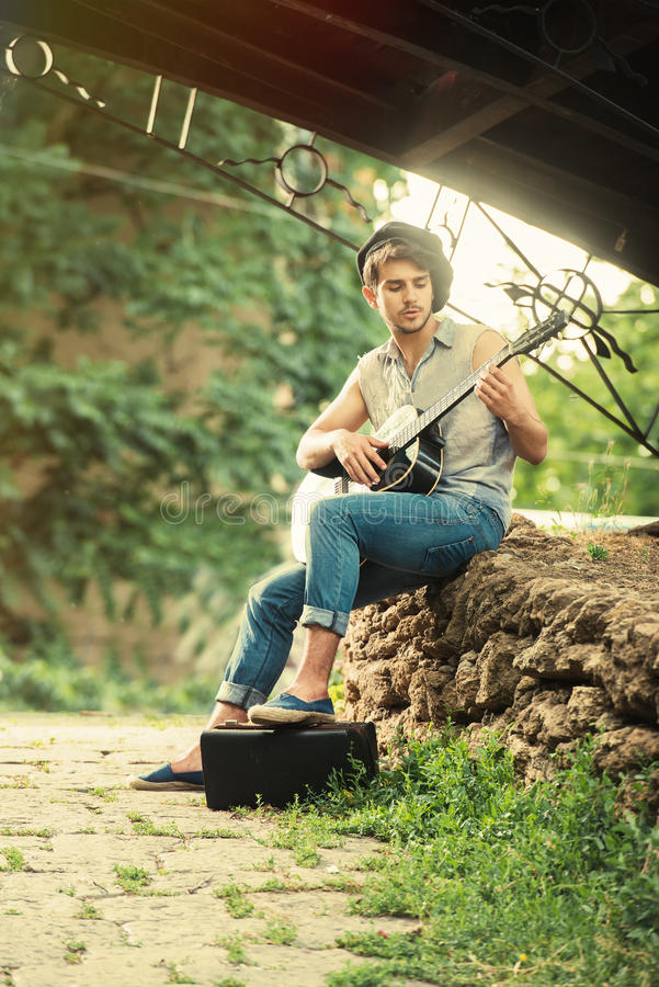 Young street guitarist. Retro style portrait of a young guitarist playing under the bridge stock photo