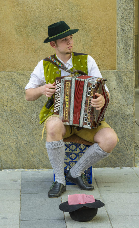 Young street performer, dressed in traditional bavarian clothes. Sing to accordion at a street corner in Marienplatz, on 12 May, 2015 in Munich, Germany stock photos