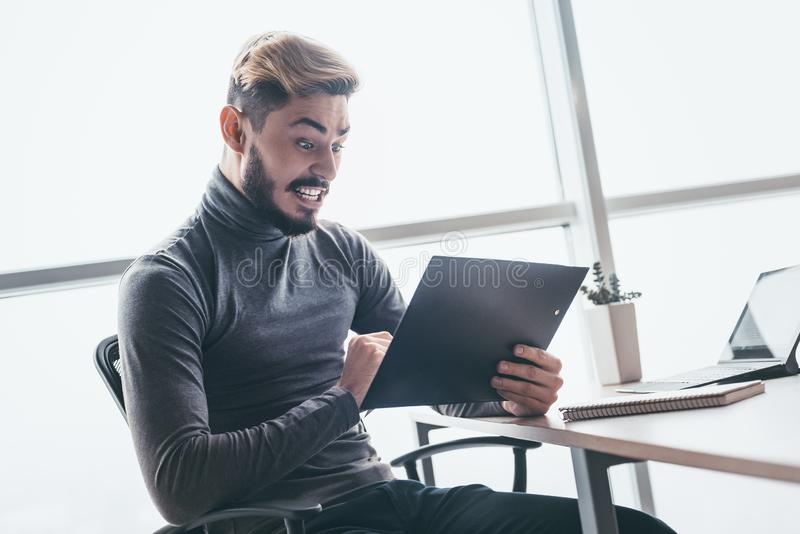 Young stressed businessman holding charts with shocked facial expression. Surprised business man looking at statistics royalty free stock photography