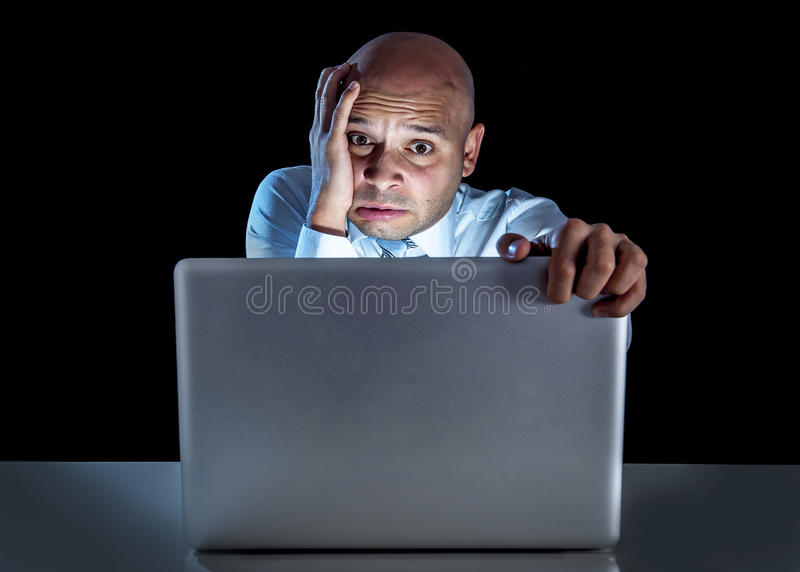 Young stressed businessman working on computer laptop late at night stock photos