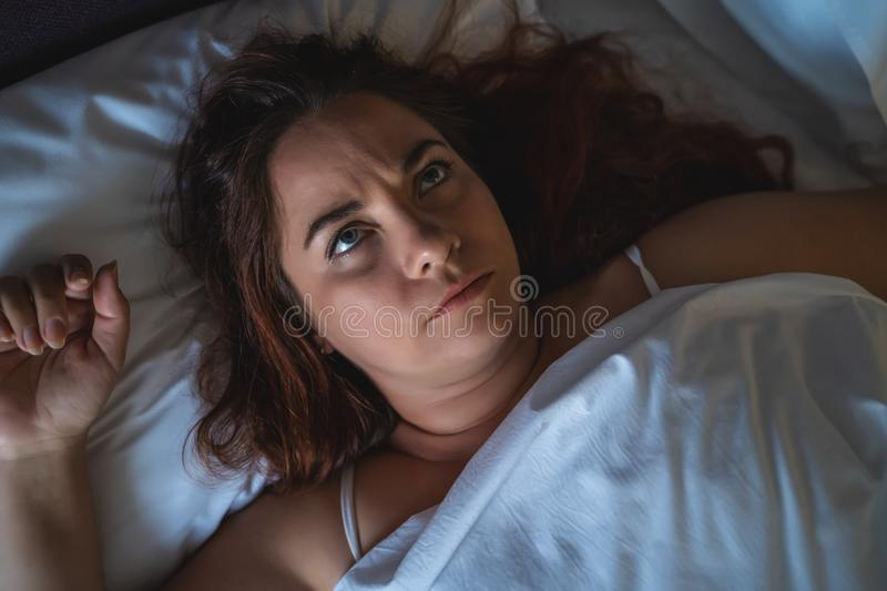 Young stressed or depressed woman lies in bed, can not sleep. Insomnia concept, top view royalty free stock photography