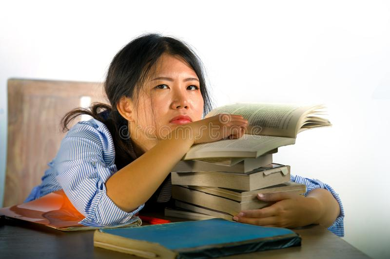 Young stressed and frustrated Asian Chinese teenager student working hard leaning on notepads and books pile on desk overwhelmed royalty free stock photo