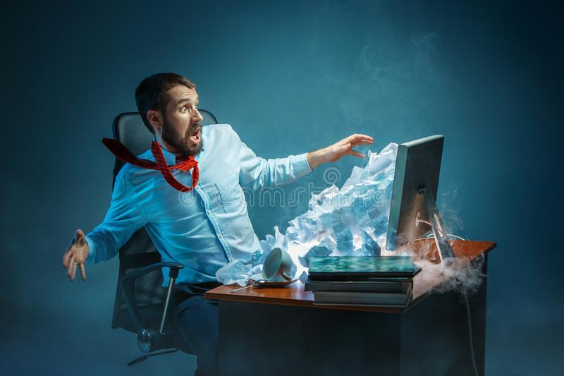 Young stressed handsome businessman working at desk in modern office shouting at laptop screen and being angry about. E-mail spam. Collage with a mountain of stock images