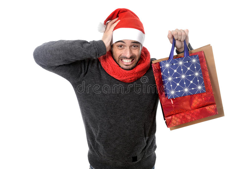 Young stressed man wearing santa hat holding red shopping bags. Young attractive shopaholic man wearing santa hat holding a lot of shopping bags looking stock photo