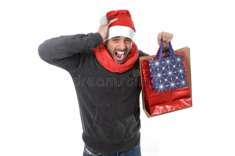 Young stressed man wearing santa hat holding red shopping bags. Young attractive shopaholic man wearing santa hat holding a lot of shopping bags looking stock photos