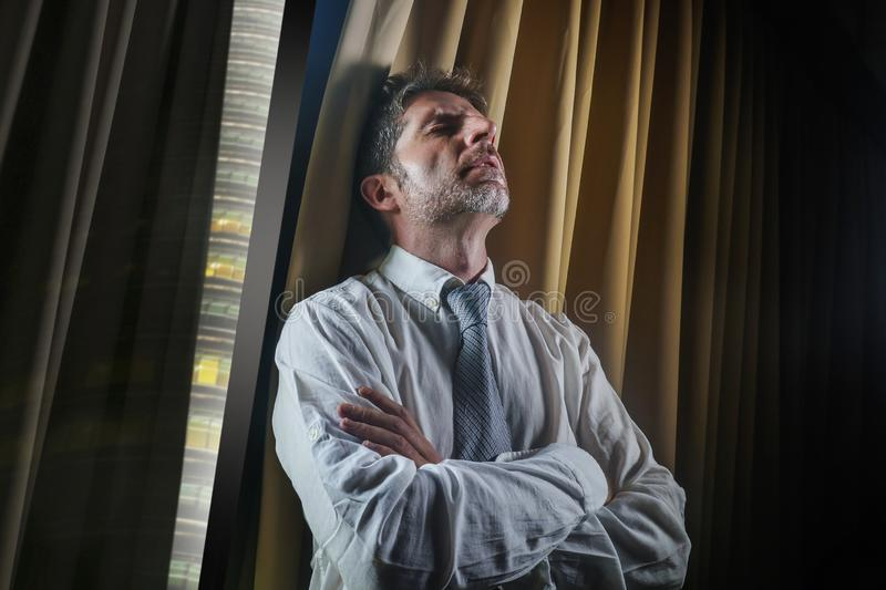 Young stressed and overwhelmed businessman working under pressure feeling depressed and worried suffering anxiety crisis leaning. Late night office portrait of stock image