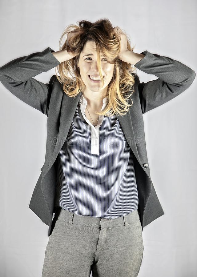 Young stressed overworked business woman. A three quarter portrait of a stressed overworked professional young business woman pulling her hair stock photo