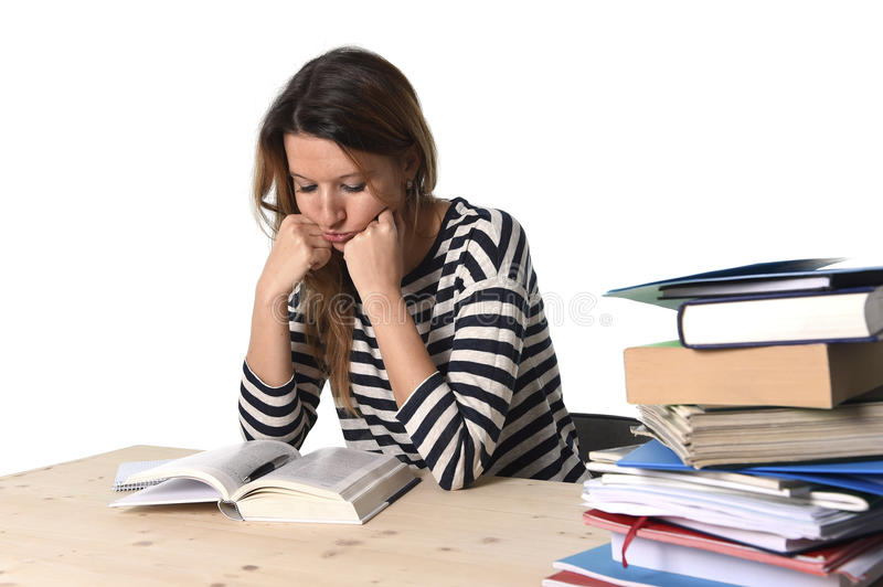 Young stressed student girl studying and preparing MBA test exam in stress tired and overwhelmed. Young stressed student girl studying pile of books on library stock photos