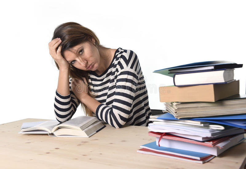 Young stressed student girl studying and preparing MBA test exam in stress tired and overwhelmed. Young stressed student girl studying pile of books on library royalty free stock photography
