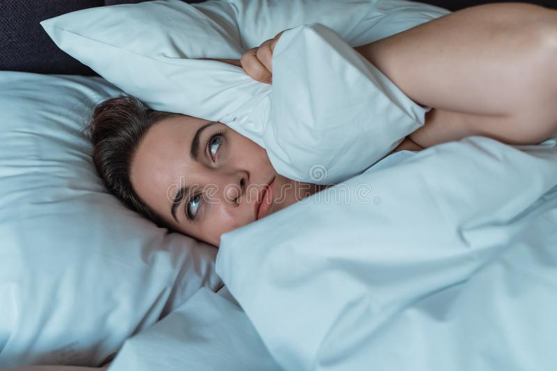 Young stressed woman cannot sleep due to noise of her neighbors from above, irritated and stressful covers her head and stock image
