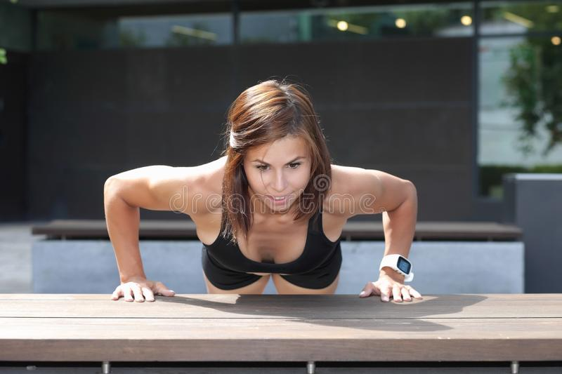 Young strong athletic girl doing push-ups stock image