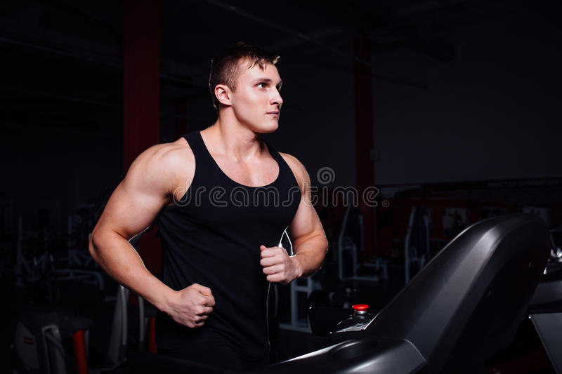 Young strong big man fitness model in the gym running on the treadmill with water bottle. stock image