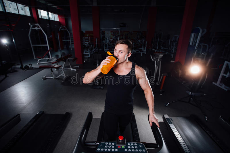 Young strong big man fitness model in the gym running on the treadmill with water bottle. royalty free stock image