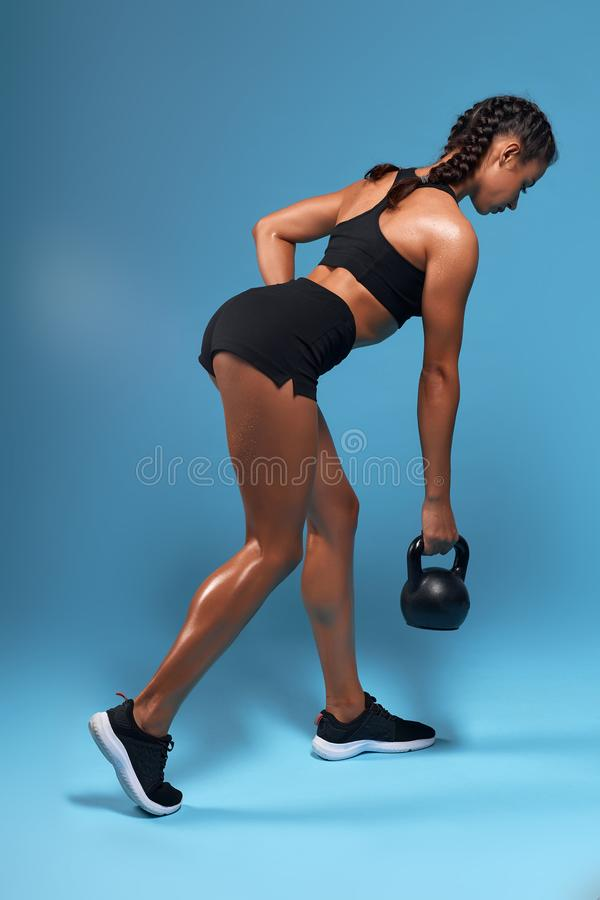 Young strong female bodybuilder swinging kettlebell, doing exercises for arms. Strength training, motivation .  blue background, studio shot. isolated blue stock images