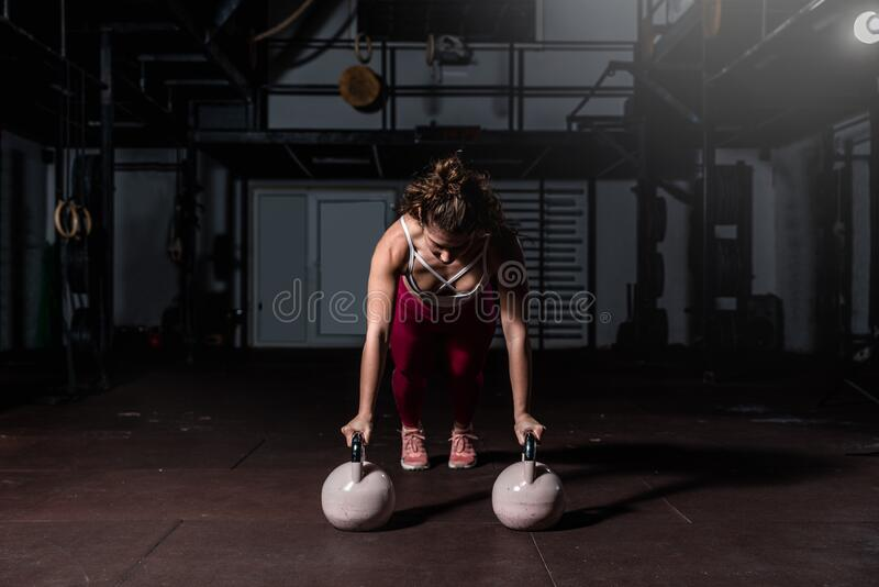 Young strong fit sweaty muscular girl with big muscles doing push ups on two big old heavy kettlebells with her hands for hard cor. E cross workout training on stock photography
