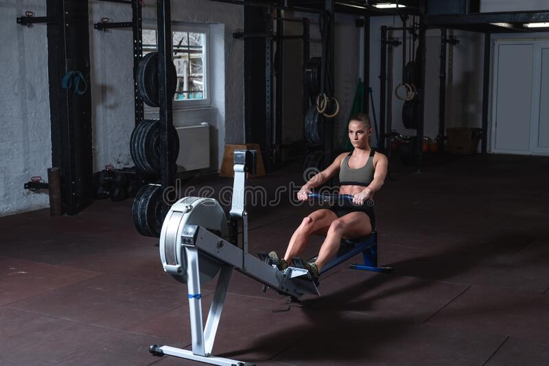 Young strong fit sweaty powerful attractive muscular woman with big muscles doing hard core row heavy cross training workout on in. Door rower at the gym real stock image