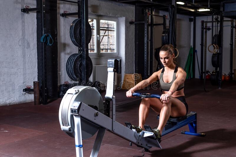 Young strong fit sweaty powerful attractive muscular woman with big muscles doing hard core row heavy cross training workout on in. Door rower at the gym real royalty free stock photography