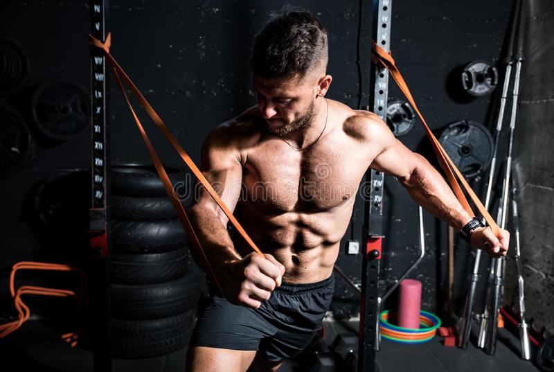 Young strong focused fit muscular man chest stretching workout in improvised gym with rubber for strength and good looking of musc royalty free stock image