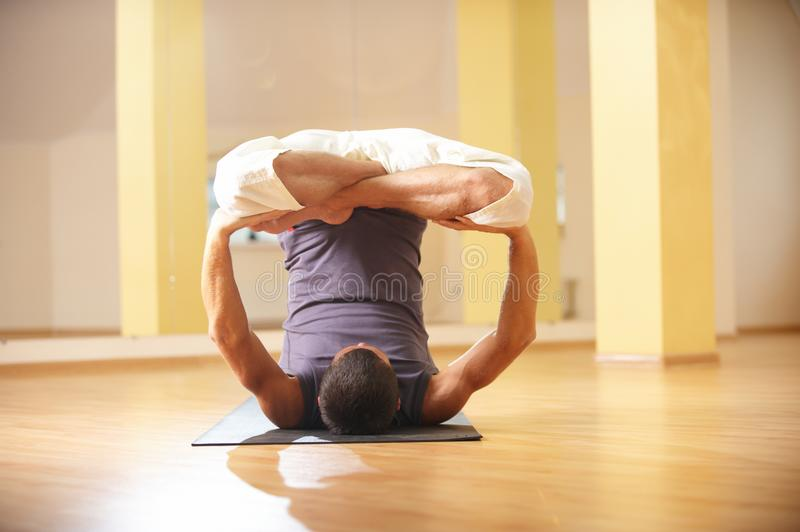 A young strong man doing yoga exercises - Urdhva Padmasana inversion lotus pose in yoga studio.  stock photo